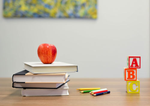 Teacher's desk with books and an apple